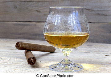 Glass of cognac with a cigar on a wooden table