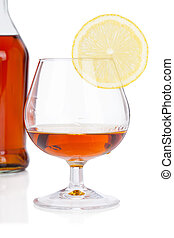 Glass of cognac with bottle on white