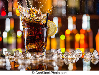 Glass of cola drink with splash on bar counter