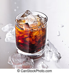glass of cola with ice and water droplets