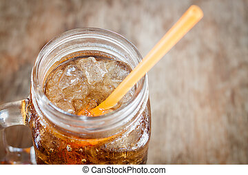 Glass of cola with ice on wooden table