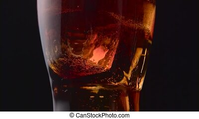 Glass of cola with white bubbles at the bottom. Black...