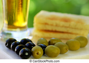 glass of cold beer with olives on green background