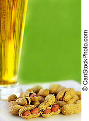 glass of cold beer with peanuts ongreen background