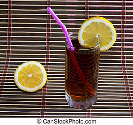 glass of cold black tea with a lemon