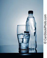 glass of cold mineral water with ice and plastic bottle. ...