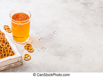 Glass of craft lager beer with pretzel snack in vintage wooden box and opener on stone kitchen table background. Beer and snack. Space for text. Top view