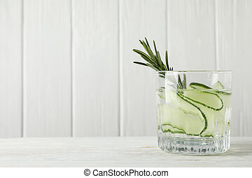 Glass of cucumber water on wooden table, close up