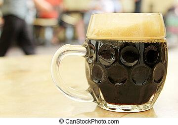 glass of dark beer with foam