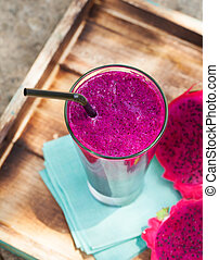 Glass of dragon fruit smoothie, juice and fresh pitahaya on...