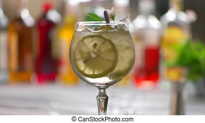 Glass of drink rotating. Drink with lemon and ice. Cool...