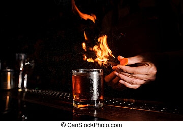 Glass of fiery cocktail on the dark bar counter