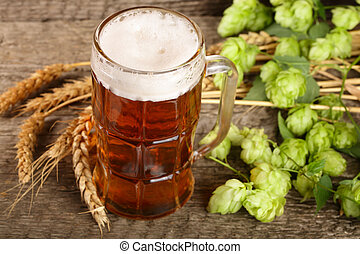 glass of foamy beer with hop cones and wheat on old wooden background