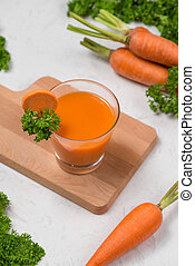 Glass of fresh carrot juice with vegetables on table.