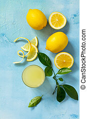 Glass of fresh freshly squeezed lemon juice on a turquoise stone or concrete table. Top view flat lay background.