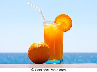 Glass of fresh orange juice and orange against the sea