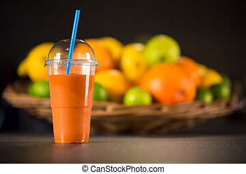 Glass of fresh smoothie made from oranges, carrots and ginger