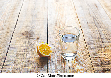 glass of fresh water with half lemon on wooden table