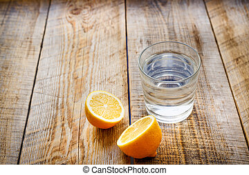 glass of fresh water with halved lemon on wooden table