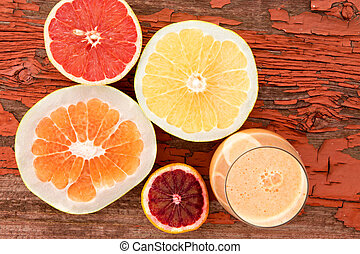 Glass of freshly liquidised grapefruit juice with halved fresh grapefruit, pomelo and ruby grapefruit on a grungy wooden background with red peeling paint and copyspace, overhead view