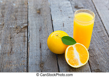 Glass of freshly pressed orange juice on wooden table