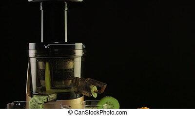 Glass of freshly squeezed fruit juice from orange and kiwi using masticating juicer