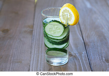 Glass of freshness water with cucumber on wooden background...