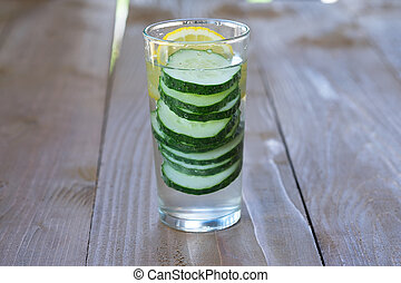 Glass of freshness water with cucumber on wooden background