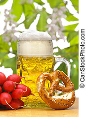 glass of german bavarian beer at munich octoberfest with radish and pretzel
