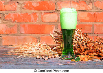 Glass of green Irish beer standing on an old table