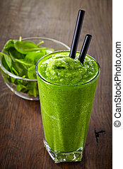 glass of green smoothie on wooden table