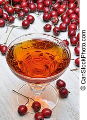 Glass of hawthorn liqueur and hawthorn fruit on a wooden ...