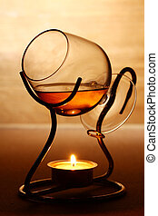 Glass of hot cognac over wooden surface