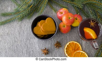 glass of hot mulled wine, cookies, apples and fir -...