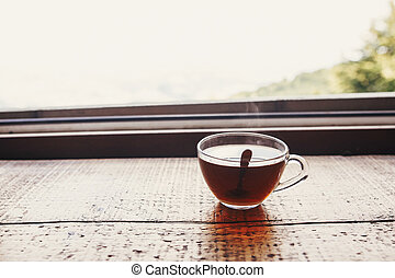 glass of hot tea on wooden table at window light with view on mountains and sky. delicious drink on mountain top. summer travel and wanderlust. space for text
