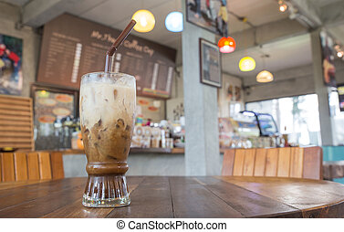 glass of ice coffee on wood table