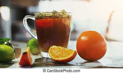 Glass of ice tea with ?hrysanthemums and orange, ice cubes on dark wooden table