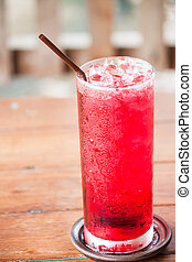 Glass of iced red drink with straw