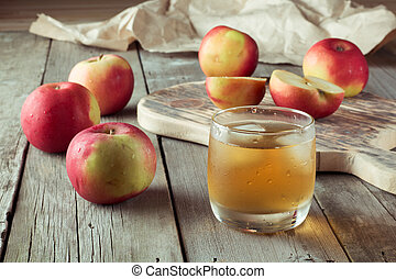 glass of juice and apples on a cutting board