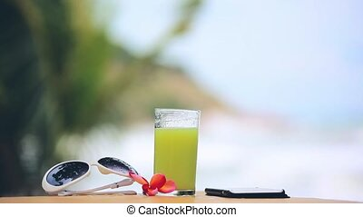 Glass of kiwi juice next to the sunglasses, mobile phone and frangipani flower on blurred bokeh background changes focus to the tropical beach. 1920x1080