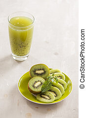 Glass of kiwi juice with fresh fruits on wooden table