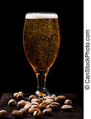 Glass of lager beer with pistachios nuts on stone board on black background. Beer and snack.