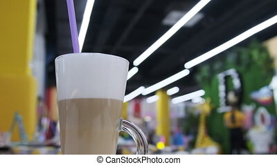 A glass of coffee latte is on a table in a cafe inside a children's entertainment center. Rest zone. Children's complex inside the shopping center, mall. 4K. Multi-colored cafe. Lifestyle.
