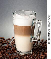 Glass of latte macchiato on the coffee beans