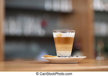 Tempting glass of latte macchiato served layered and topped with cream on a saucer on a bar counter in a restaurant or coffee house