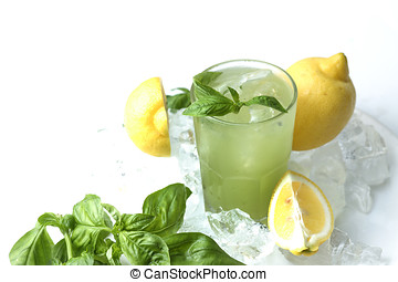 Glass of lemonade with basil leaves and lemons in ice cubes isolated on white background