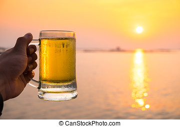 Glass of light beer at the beach