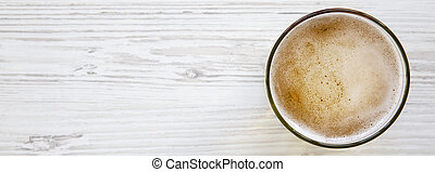 Glass of light beer on a white wooden surface. Copy space.