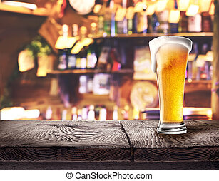 Glass of light beer on wooden board on the bar's background