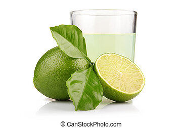 Glass of lime juice and lime fruits with green leaves isolated